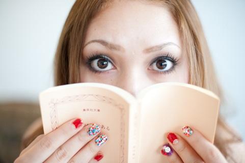 本で口を塞ぐ女性