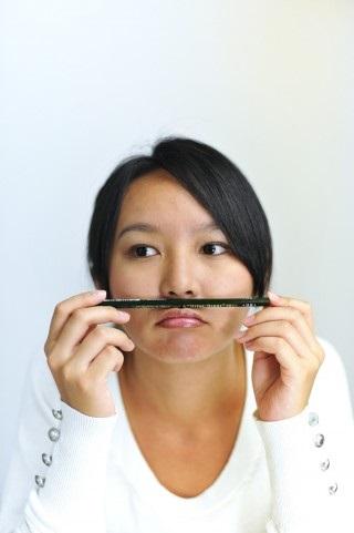 鉛筆を鼻に乗せる女性